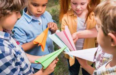Pod of Elementary School kids making paper airplanes